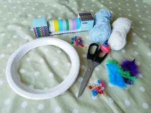 Art and craft supplies, paper plate, scissors, beads, wool, hole punch, colourful feathers, colourful tape. 4 freckled faces.